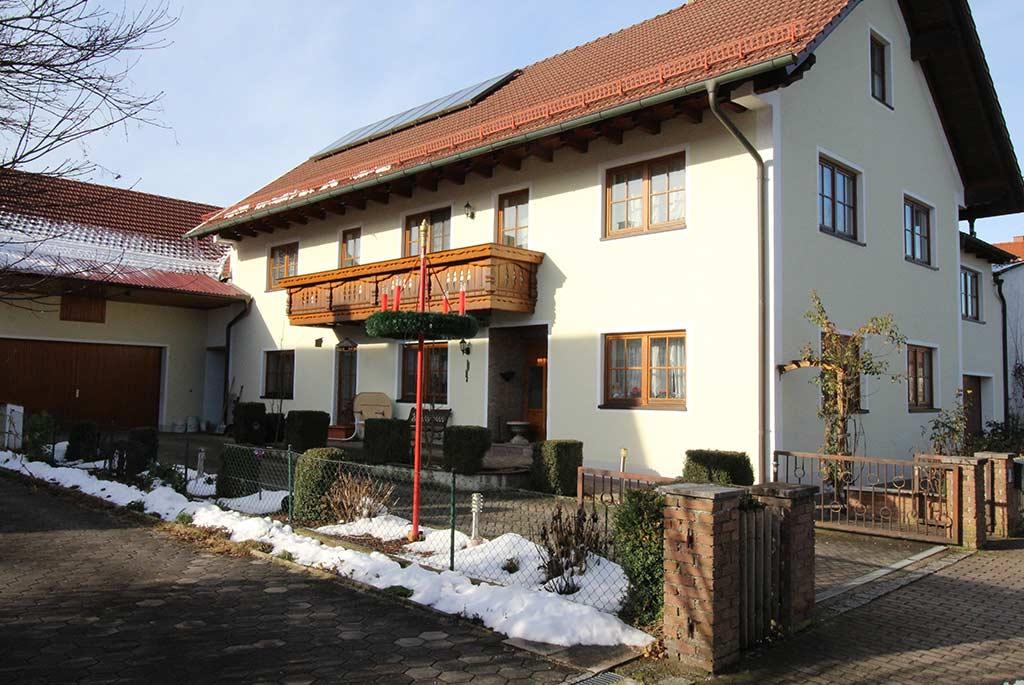Bauernhaus mit Lasuranstrich, im Vordergarten ein Fahnenmast mit Adventskranz