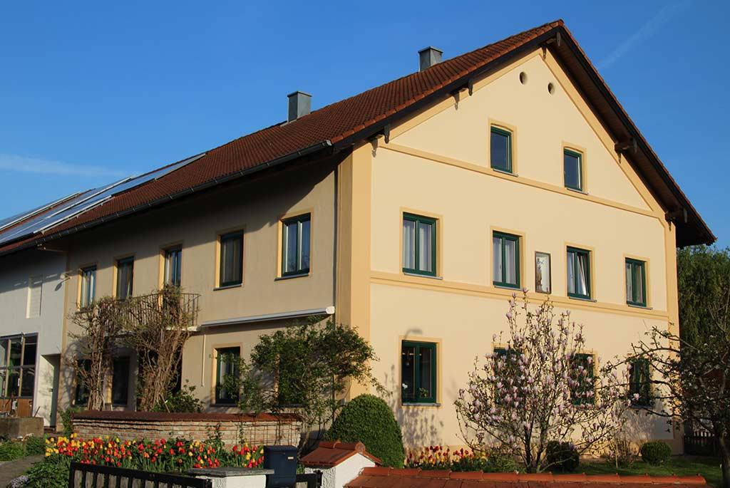 Altes Bauernhaus mit beige-gelber Fassadenfarbe und grünen Holzfenstern