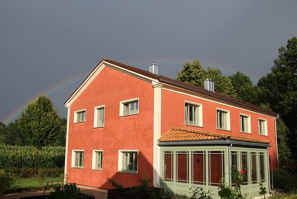 Roter Hausanstrich mit weiß-grünen Fensterrahmen und einem grünen Wintergarten