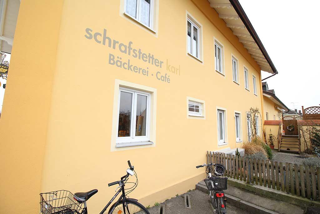 """Fassadengestaltung in Gelb mit Firmenschriftzug """"Schrafstetter Karl Bäckerei - Cafe"""""""