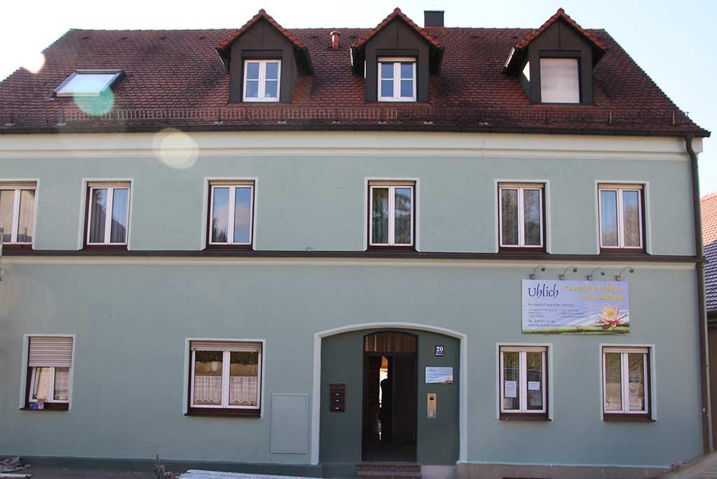 Grüne Hausfassade, Eingang und Fenster mit weißen Highlights, an der Hausfront hängt ein Werbebanner