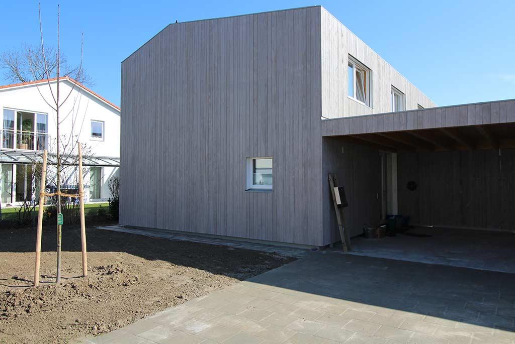 Massivhaus mit grauer Holzverschalung und angesätem Rasen mit Baum im Vordergrund