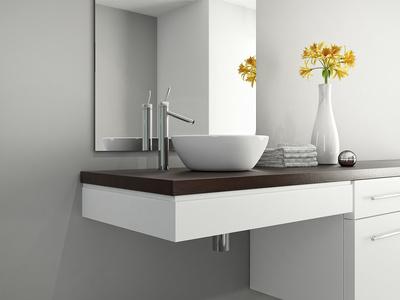 Weißes Designerwaschbecken vor grauer fugenloser Wand mit Spiegel