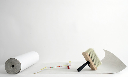 Tapezierpinsel steht auf weißer Tapetenrolle