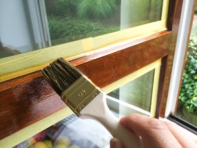 Holzfensterrahmen wird mit Pinsel lasiert