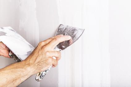 Mann verspachtelt weiße Wand