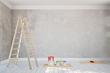 Leiter und bunte Farbeimer vor grau getupfter Wand