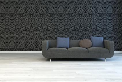 Dunkelgraues Sofa mit Kissen vor einer Fototapete mit Ornamenten