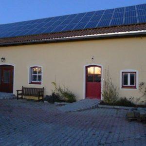 Ockerfarbenes Gebäude mit Solarkollektoren auf dem Dach und roten Türen und Fenstern
